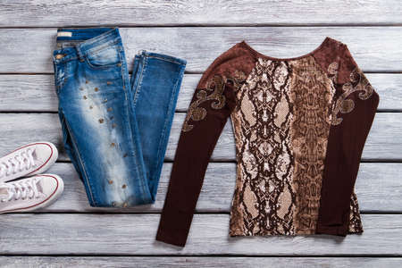 pullover: Blue jeans and brown top. Girls brown long sleeve top. Imported merchandise on store showcase. Best clothing in outlet shop.