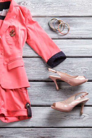 open toe: Salmon short suit and heels. Open toe heels and clothing. Designer clothes for girls. Summer apparel in showroom. Stock Photo