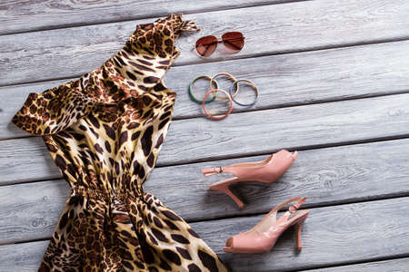 open toe: Leopard dress and heel shoes. Open toe heels and sunglasses. New asymmetric dress on display. Luxury outfit with accessories.
