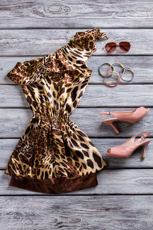 open toe: Open toe heels and dress. Leopard dress and sunglasses. Evening clothes on gray shelf. Girls prom apparel with accessories.