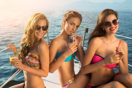 Girls with drinks on yacht. Ladies in swimsuits smiling. Young and happy. Bright smiles of beautiful women.