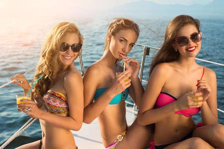 Mädchen mit Getränken auf der Yacht. Damen in Badeanzügen lächelnd. Jung und glücklich. Helles Lächeln der schönen Frauen.