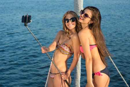 carelessness: Girls with selfie stick smiling. Ladies on yacht taking selfies. Capturing the funniest moments. Carelessness and joy.