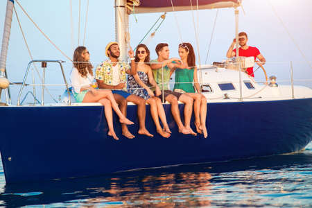 told: People sitting on a yacht. Young guys and girls smiling. Stories told by a friend. When we were young. Stock Photo