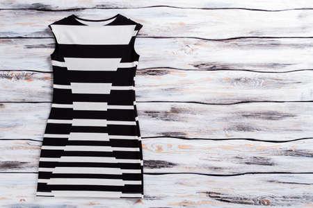 sleeveless dress: Casual black and white Sleeveless dress on wooden background.