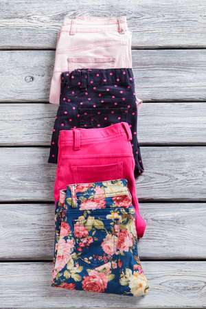 outlet store: Dotted and floral trousers. Bright folded pants laying closely. New arrivals in outlet store. Quality merchandise from abroad.