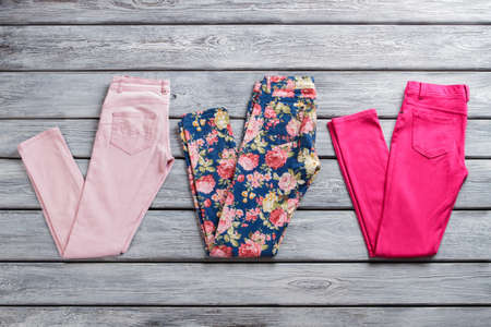 informal clothes: Pink and blue trousers. Pairs of folded casual pants. Brand new clothing in stock. Sale of goods from abroad.