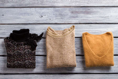 pullover: Sweaters of different color on wooden background. Stock Photo