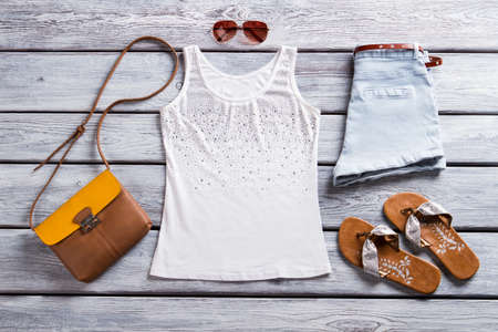 flops: White tank top and sunglasses. Brown flip flops and purse. Stock Photo