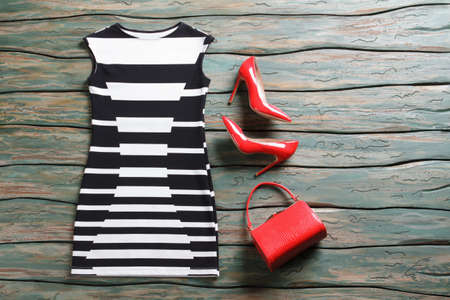 woman's clothing: Sleeveless dress and heel shoes. Bright red purse and heels. Attractive evening outfit for summer. Womans clothing on auction.