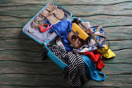 overfilled: Opened suitcase with crumpled clothes. Sandals and bracelets in luggage bag. Stock Photo