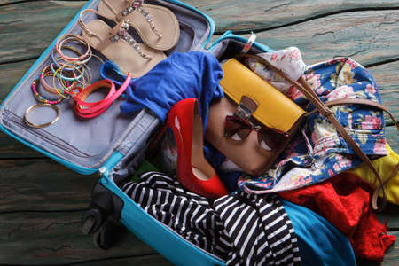 overfilled: Red heel shoe in suitcase. Crumpled clothes in luggage bag. Stock Photo