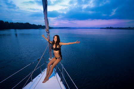 outstretched arms: Girl with wineglass on yacht outstretched arms.