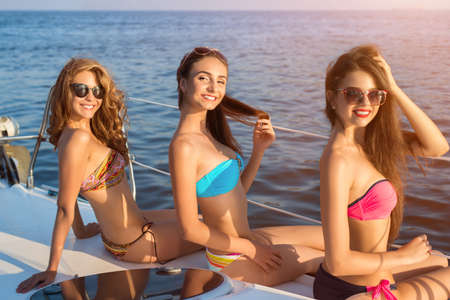 flirtation: Smiling women on a yacht. Stock Photo