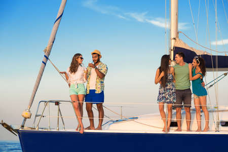 evening: Smiling people on yacht deck. Stock Photo