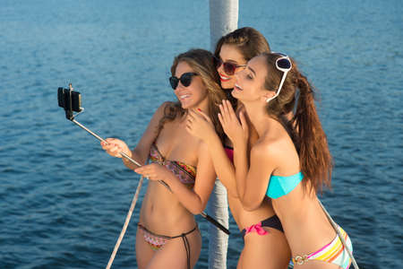 Smiling girls take a selfie on yacht. Stock Photo