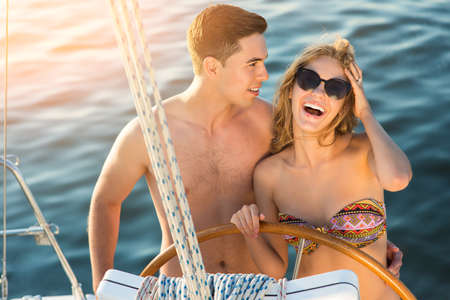cruise travel: Smiling couple near yacht wheel.