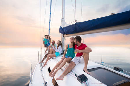 Young people sitting on yacht.