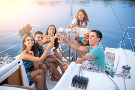 People with drinks taking selfies on yacht.