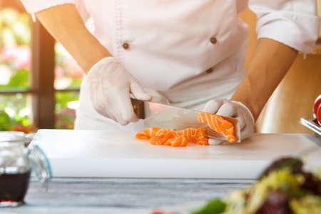 Hand with knife cutting fish. Standard-Bild