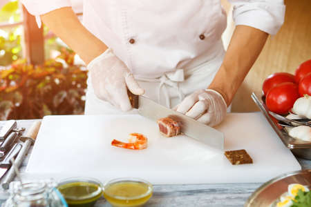 cutting meat: Hand with knife cutting meat. Stock Photo