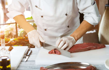 Man cutting meat with knife. Stock Photo