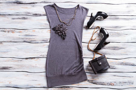 designer bag: Gray evening top and necklace. Flower applique top with bag. Designer clothes and classy footwear. Dark evening outfit on display.