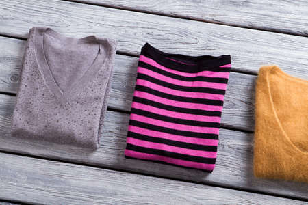 womans clothing: Pink striped sweater. Folded pullovers of different color. Womans sweatshirt on gray table. Autumn clothing at low price. Stock Photo