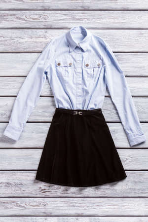table skirt: Light shirt and black skirt. Casual blue shirt with pockets. New items in fashion boutique. Clothing on gray wooden table. Stock Photo