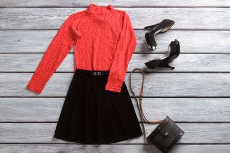 heel strap: Red top and black skirt. Dark heel shoes and handbag. Spring sale in brand shop. Attractive female clothes and accessory.