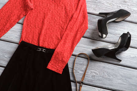 long sleeves: Black skirt and heel shoes. Red top with long sleeves. Luxury clothing on wooden table. Femininity and charm.