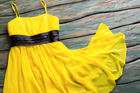 lady's: Yellow summer dress. Casual dress with black insert. Ladys garment on green shelf. Clothing item for young girls. Stock Photo