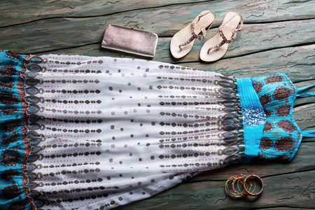 modest: Long summer dress and sandals. Silver clutch bag and bracelets. Green wooden table with clothes. Modest outfit with small purse.