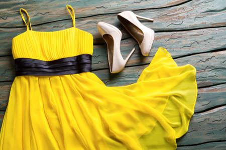 Gelbes Kleid und beige Fersen. Glatte Fersen der hellen Farbe. Kleidung auf grünem hölzernem Hintergrund. Einfache Abendausstattung des Mädchens. Standard-Bild