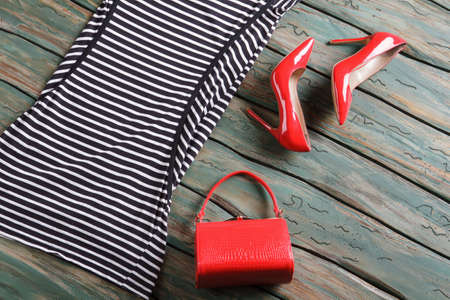 designer bag: Red glossy heel shoes. Striped dress and a bag. Designer footwear on wooden table. Clothing bought at auction.