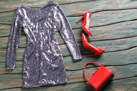 tacones rojos: vestido brillante de color plateado. tacones rojos y vestido de noche. La ropa del diseñador para las niñas. estante de madera verde con la ropa. Foto de archivo