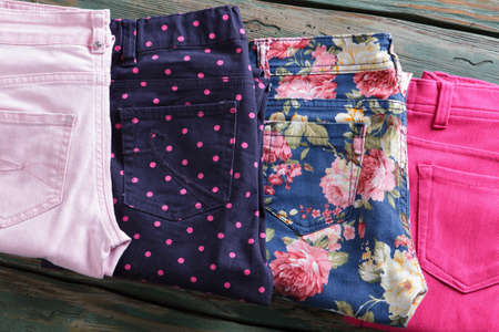 outlet store: Blue floral pattern pants. Folded bright pink trousers. Womans pants in outlet store. Newly purchased clothing on shelf.