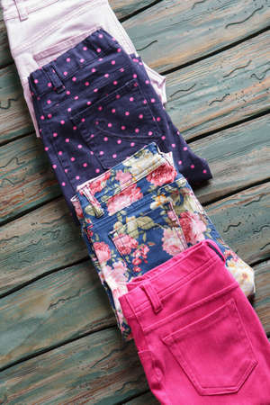 outlet store: Pants with pink floral print. Folded trousers of navy color. New cotton pants on shelf. Quality items in outlet store.