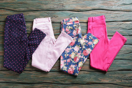 discounted: Dark trousers with dotted print. Colorful pink folded pants. Discounted goods in outlet shop. Last sizes at special price.