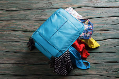 piece of luggage: Luggage bag filled with clothes. Things fall out of suitcase. Summer essentials only. Packing bag and making mess.