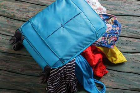 overfilled: Blue overfilled suitcase. Luggage bag filled with clothing. Suitcase on green wooden floor. Vacation is waiting.
