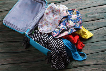 rag wheel: Opened suitcase with clothes. Crumpled clothes inside luggage bag. You have forgotten something. Leaving home in a hurry.
