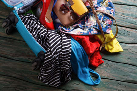 rag wheel: Crumpled clothes in blue suitcase. Heel shoe in opened bag. Trip will take a while. Just a few more things.