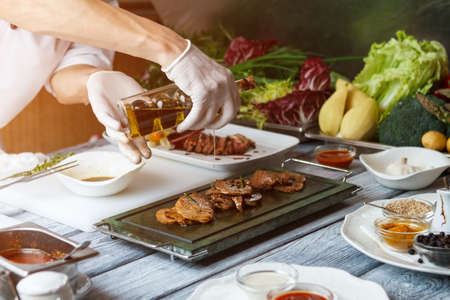 hand holding bottle: Hand holding bottle with liquid. Liquid dripping on cooked meat. Olive oil for veal medallions. Delicious meat cooked at restaurant.