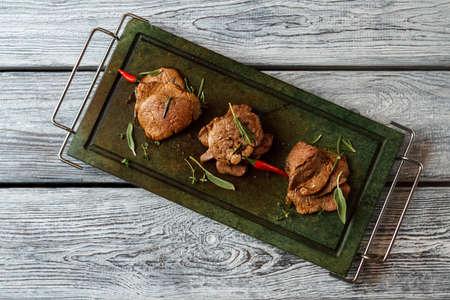 manjar: bandeja verde con carne cocinada. Pimienta de chile y carne oscura. Degustar la delicadeza. medallones de ternera en la bandeja de piedra.