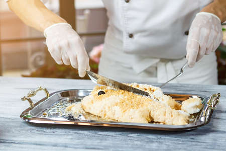 breading: Hand with spatula touches fish. Tray with breaded fish. Cooked dorado fish in breading. Chef working with seafood.
