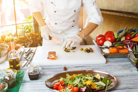 tiger shrimp: Hands with knife cut olives. Vegetable salad on tray. Green olives and tiger shrimp. Restaurant chef has serious skills.