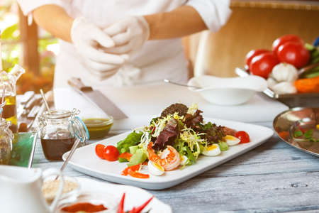 european cuisine: Salad on white plate. Man standing near salad plate. Anchovy tapenade and quail eggs. European cuisine at the restaurant. Stock Photo