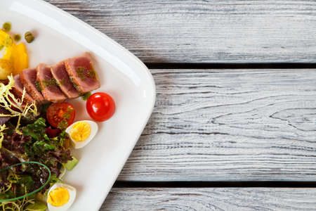 european anchovy: Plate with salad. Salad with tomatoes and meat. Quail eggs and fried tuna. Organic meal served at bistro.