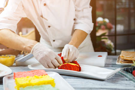 custard slices: Hands with slices of strawberry. Pieces of berry on plate. Pastry chef cooks flan. Sweet custard and juicy fruit.